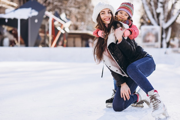 スケートリンクでアイススケートを教える娘と母 無料写真