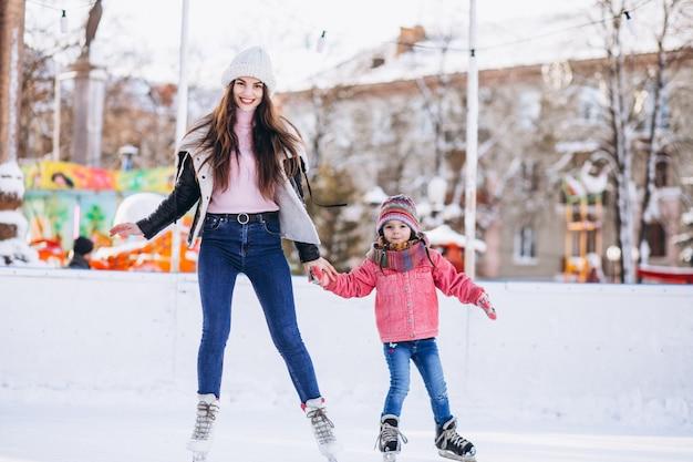 Мать с дочерью учат катанию на коньках на катке Бесплатные Фотографии