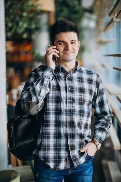 Молодой человек в кафе стоял у окна и разговаривает по телефону Бесплатные Фотографии