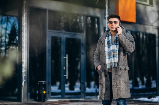 電話を使用して外の若いハンサムな男 無料写真