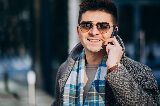 Молодой красивый мужчина на улице с помощью телефона Бесплатные Фотографии