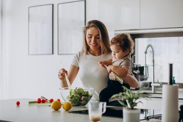 Молодая мать с сыном делает салат на кухне Бесплатные Фотографии