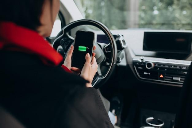 Женщина заряжает машину и смотрит на телефон Бесплатные Фотографии