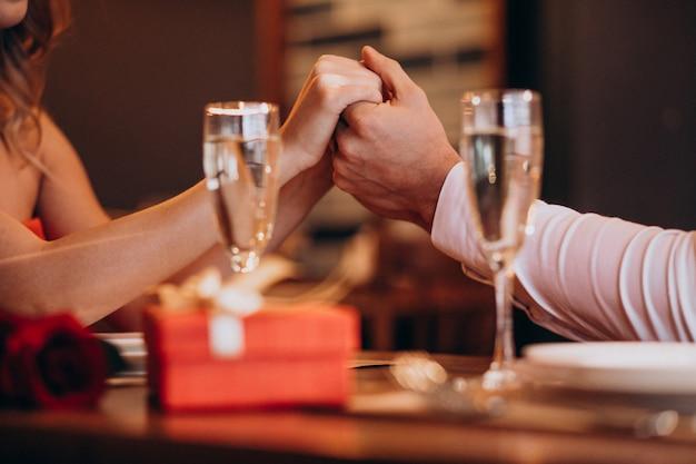 レストランでバレンタインの夜に手を繋いでいるカップル 無料写真