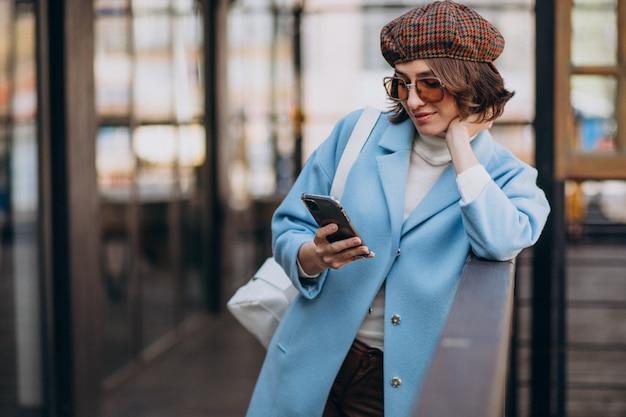 電話を使用して、カフェで青いコートの若い女性モデル 無料写真