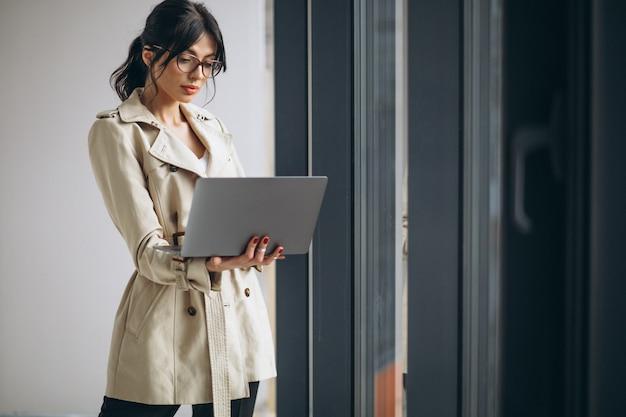 オフィスの窓のそばに立っているラップトップを持つ若いビジネス女性 無料写真