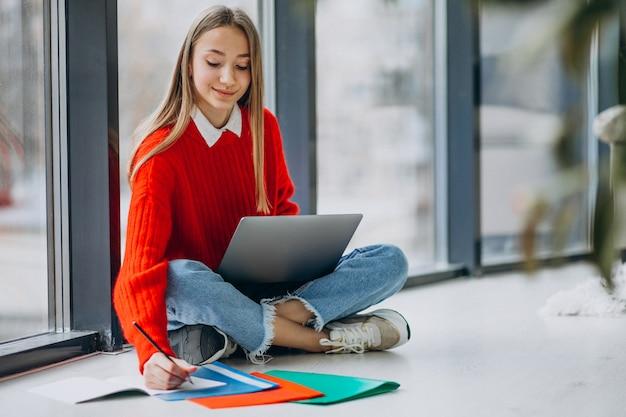 Студентка учится на компьютере у окна Бесплатные Фотографии