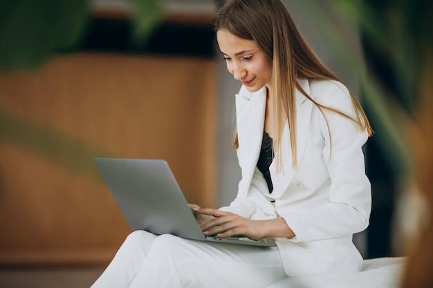 コンピューターに取り組んでいる白いスーツの若いビジネス女性 無料写真