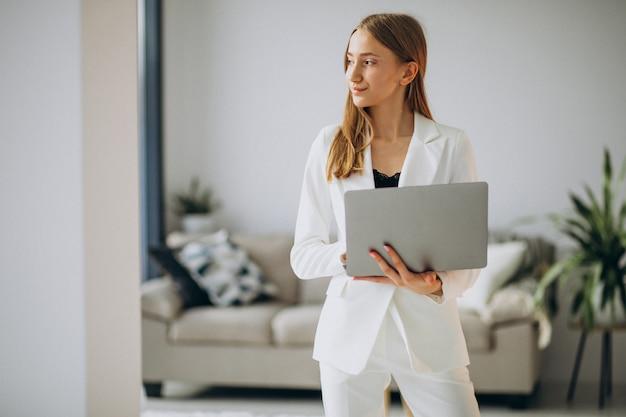 Молодая бизнес-леди в белом костюме работая на компьютере Бесплатные Фотографии