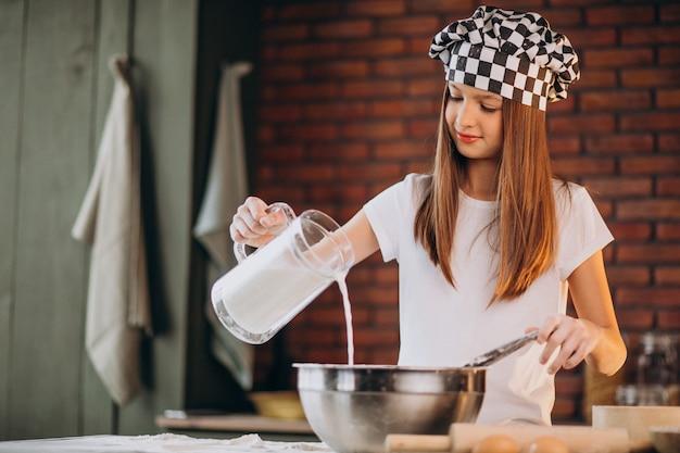 朝食のキッチンでペストリーを焼く少女 無料写真