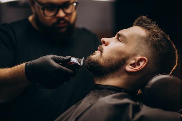 Красивый мужчина стричь бороду в парикмахерской Бесплатные Фотографии
