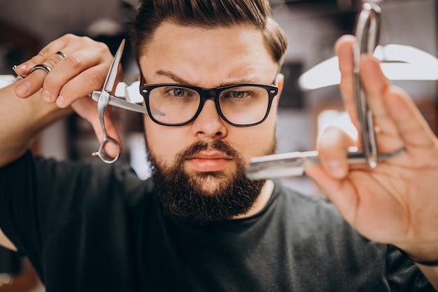 理髪ツールを持つプロのヘアスタイリストをクローズアップ 無料写真