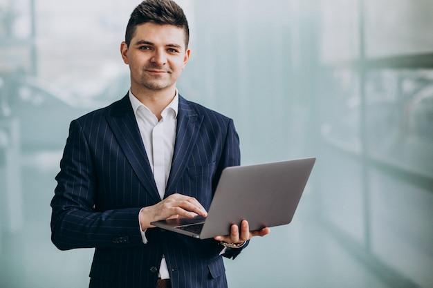 オフィスでラップトップを持つ若いハンサムなビジネス男 無料写真
