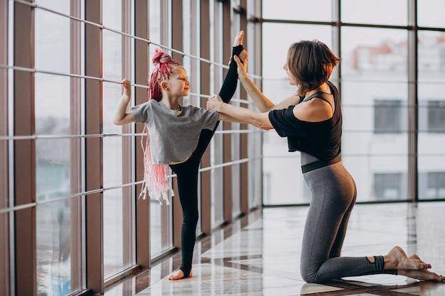 ウィンドウでヨガの練習の小さな娘を持つ母 無料写真