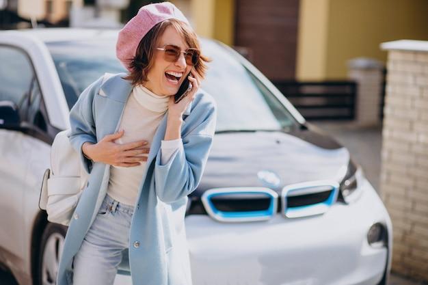 彼女の電気自動車で電話で話している若い女性 無料写真