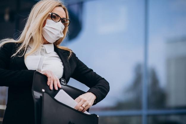ビジネスセンターの外のマスクを身に着けているビジネス女性 無料写真