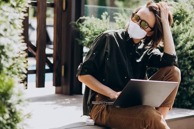 マスクで自宅からコンピューターに取り組んでいる若いビジネス女性 無料写真