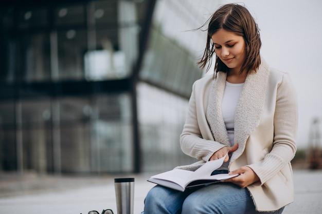 若い女の子に座って本を読んで、通りの外でコーヒーを飲む 無料写真