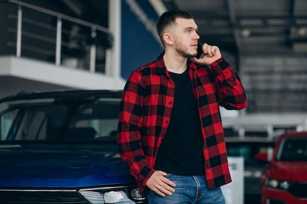 若い男が車のショールームで車を選ぶ 無料写真