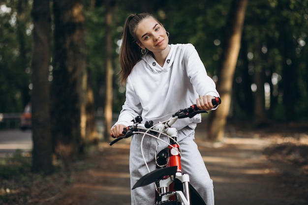 Молодая спортивная женщина езда на велосипеде в парке Бесплатные Фотографии