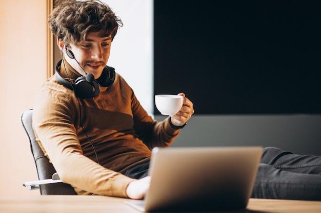 Красивый молодой деловой человек работает на компьютере и пить кофе Бесплатные Фотографии