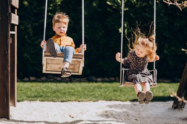 Мальчик и девочка веселятся на качелях Бесплатные Фотографии