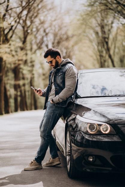 Красивый мужчина стоял у машины в парке Бесплатные Фотографии