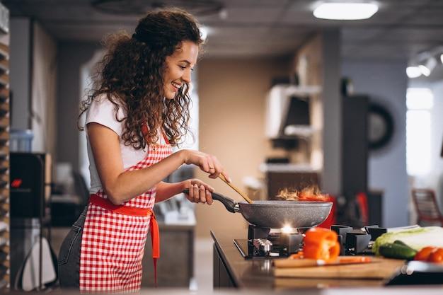 女性シェフが鍋で野菜を調理 無料写真