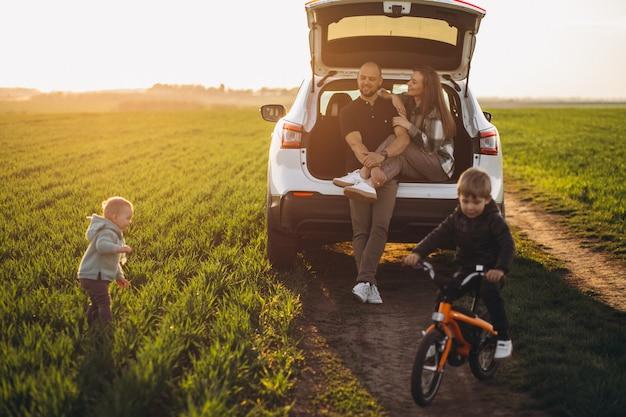 車で旅行する子供たちと若い家族がフィールドに立ち寄った 無料写真