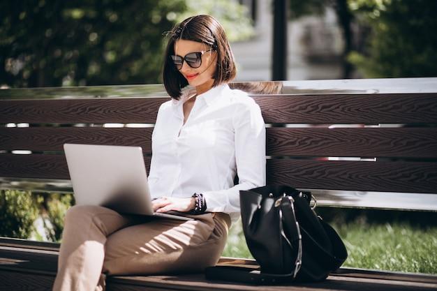 公園の外のラップトップに取り組んでいるビジネス女性 無料写真