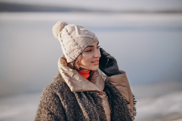 湖で冬に電話で話す女性 Premium写真