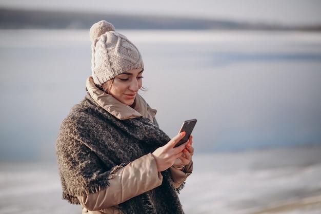 湖で冬に電話を持つ女性 Premium写真