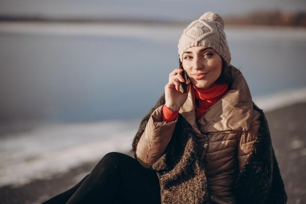 電話で話し、湖でベンチに座っている女性 Premium写真