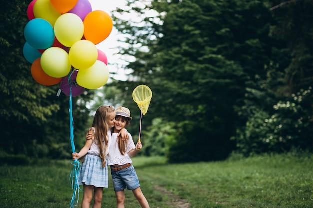Маленькие девочки-друзья с воздушными шарами в лесу Бесплатные Фотографии