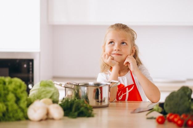 キッチンで何を料理するか考えている少女 無料写真