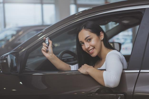ディーラーで新しい車を買う素敵な若い女性 Premium写真