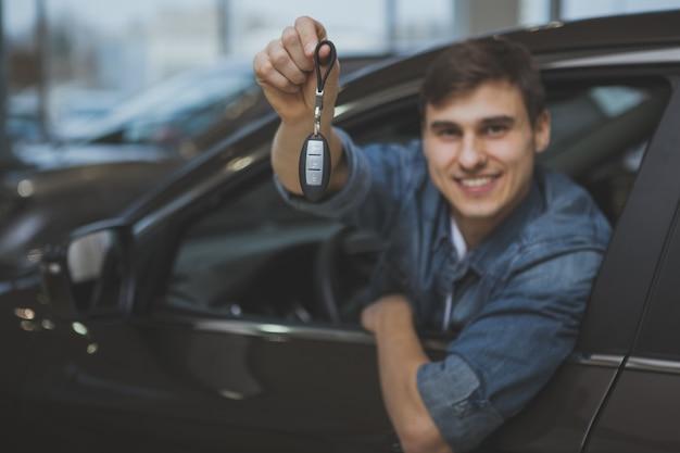 購入する新しい自動車を選択するハンサムな男 Premium写真