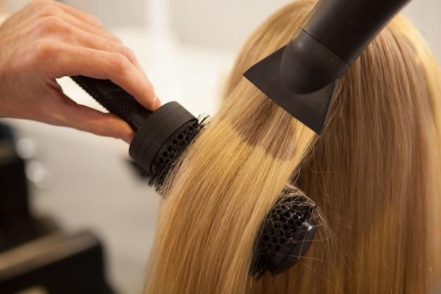 彼女の髪を美容院でスタイリングを持つ若い女性 Premium写真