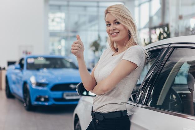 幸せな笑顔の新しい車を買うゴージャスな女性。 Premium写真