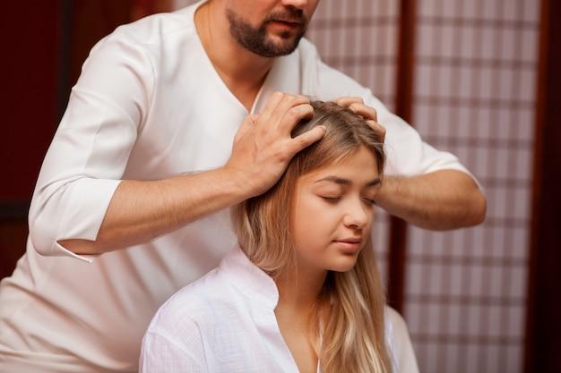プロのタイのマッサージ師が彼女の頭をマッサージしながら、嬉しそうに笑って美しい穏やかな女性。タイのスパセンターでヘッドマッサージを受ける魅力的な女性。ストレス解消、癒し、健康 Premium写真