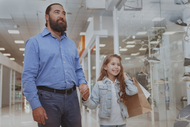 ショッピングモールで彼女の父親と一緒に買い物にかわいい女の子 Premium写真