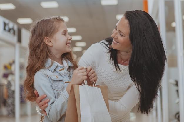 彼女の母親と一緒にモールでショッピングかわいい女の子 Premium写真
