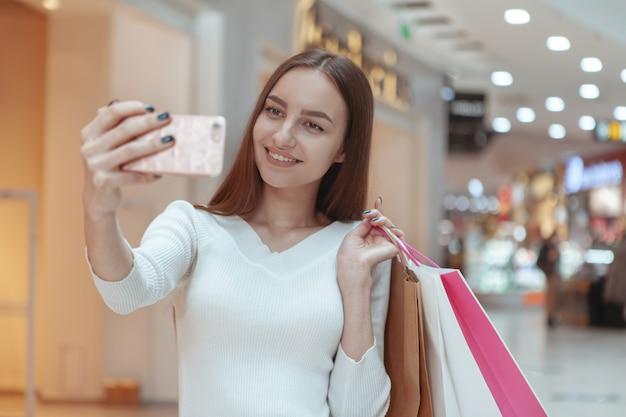 Красивая молодая женщина, покупки в местном торговом центре Premium Фотографии