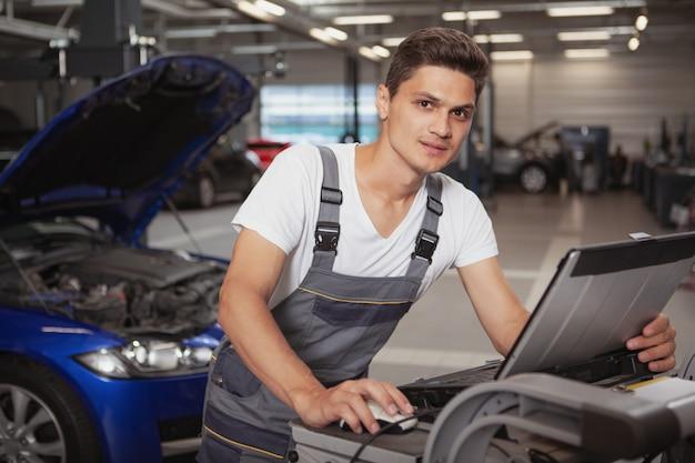 彼のガレージで若いハンサムな自動車修理工車両 Premium写真