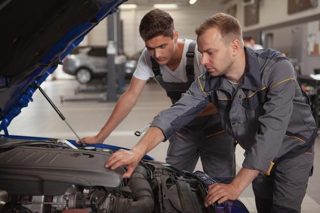 Два мужских механика работают в гараже Premium Фотографии