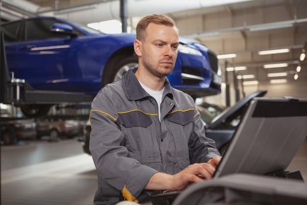 ガレージで働く成熟した男性自動車整備士 Premium写真