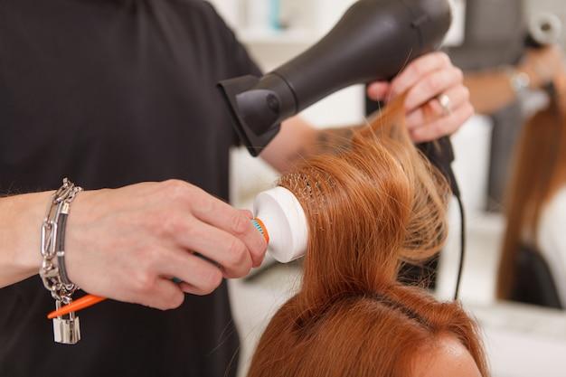 女性のクライアントの髪をスタイリングする美容師 Premium写真