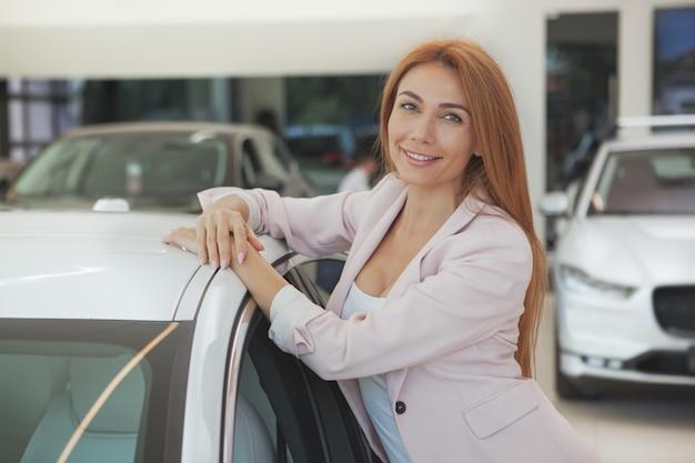 ディーラーで新しい車を選ぶ豪華な女性 Premium写真