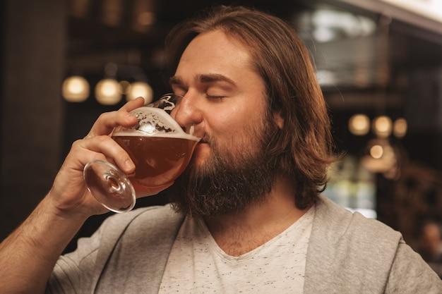 パブでビールを飲んで楽しんでいるひげを生やした若い男 Premium写真