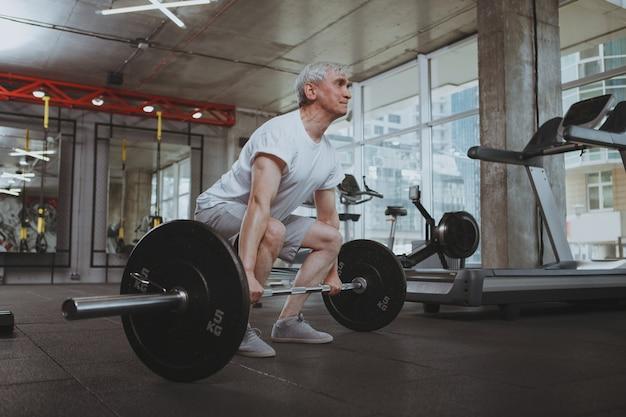 Старший мужчина работает в тренажерном зале Premium Фотографии